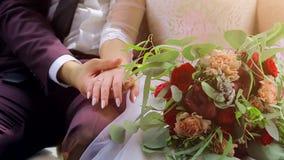 O close up dos noivos é de assento e guardando as mãos O noivo guarda a mão do ` s da noiva vídeos de arquivo