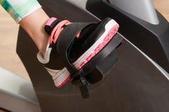 O close up dos pés da jovem mulher está no pedal estacionário da bicicleta Imagem de Stock Royalty Free
