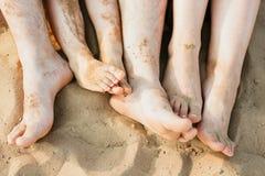 O close up dos pés enfileira o encontro na linha na praia do verão imagem de stock royalty free