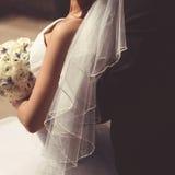 O close up dos pares dos noivos, vestido de casamento do véu com ramalhete floresce Foto de Stock