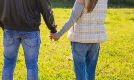O close-up dos pares no amor que anda no outono estaciona guardar as mãos que olham no por do sol Foto de Stock Royalty Free