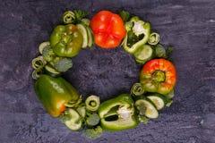 O close-up dos pepinos e dos brócolis búlgaros da pimenta alinhou em um círculo em um fundo preto Imagens de Stock