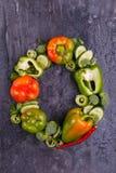 O close-up dos pepinos e dos brócolis búlgaros da pimenta alinhou em um círculo em um fundo preto Imagem de Stock