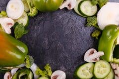 O close-up dos pepinos e dos brócolis búlgaros da pimenta alinhou em um círculo em um fundo preto Imagem de Stock Royalty Free
