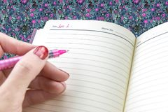 O close up dos woman's entrega pronto para escrever na agenda pessoal em n Fotografia de Stock