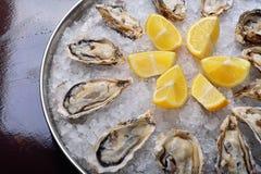 O close-up em ostras congela, limão e a água espirra Fotografia de Stock Royalty Free