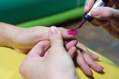 O close-up em pregos pintou o vermelho em um descanso amarelo Imagem de Stock Royalty Free