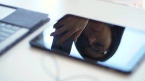 O close-up, em um desktop branco, ao lado de um portátil, a cara de uma mulher de negócio com vidros é refletido na tabuleta filme
