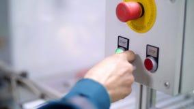 O close-up, em um protetor especial, a mão pressiona a tecla 'Iniciar Cópias' verde, ao lado da vermelho-parada filme