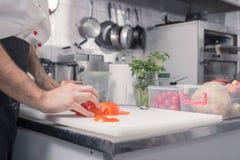 O close up entrega a cozinha do cozinheiro chefe, cortando tomates Imagem de Stock Royalty Free