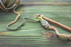 O close up faz crochê a foto chain Rústico fazer crochê a linha e um gancho de bambu Aqueça a bola verde do fio do inverno para f Imagem de Stock Royalty Free