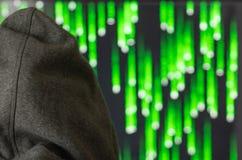 O close-up, hacker na capa olha o monitor, o conceito da segurança informática fotografia de stock