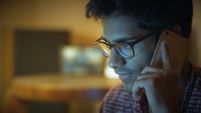 O close-up, homem indiano bonito nos vidros fala sobre o telefone e olha o tela de computador video estoque