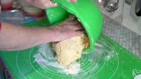 O close-up, mão de uma mulher adulta espalhou uma massa cortada de uma bacia verde em uma mesa de cozinha vídeos de arquivo
