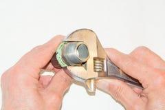 O close up a mão masculina girou a chave de chave inglesa da porca Imagem de Stock