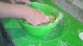 O close-up, mãos de uma mulher idosa amassa a massa em uma bacia verde em uma mesa de cozinha filme
