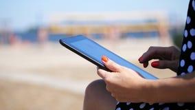O close-up, mãos fêmeas com tratamento de mãos vermelho brilhante, menina trabalha em uma tabuleta, na praia, em um dia de verão  vídeos de arquivo