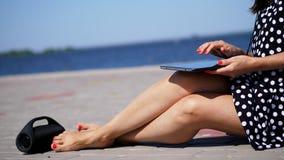 O close-up, menina trabalha em uma tabuleta, mãos fêmeas, pés com tratamento de mãos vermelho brilhante, pregos, na praia, em um  filme