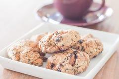 O close up misturou cookies da porca com o copo de café violeta Imagens de Stock Royalty Free