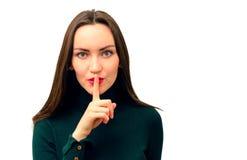 O close-up moderno e bonito da menina põe um dedo a seus bordos no sinal do silêncio fotos de stock royalty free