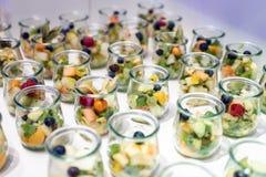 O close up muito frasco da sobremesa enfileirou acima na tabela de bufete com geleia e creme de frutos frescos Foto de Stock