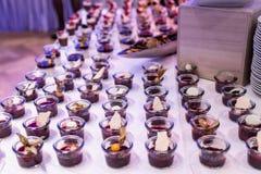 O close up muito frasco da sobremesa enfileirou acima na tabela de bufete com geleia e creme de frutos frescos Fotografia de Stock