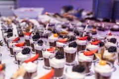 O close up muito frasco da sobremesa enfileirou acima na tabela de bufete com geleia e creme de frutos frescos Foto de Stock Royalty Free