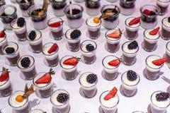 O close up muito frasco da sobremesa enfileirou acima na tabela de bufete com geleia e creme de frutos frescos Imagens de Stock Royalty Free
