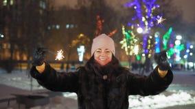 O close-up, mulher alegre balança luzes de Bengal no parque para o Natal filme