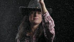 O close-up, a mulher bonita em um vaqueiro Hat e a camisa de manta regada com a neve disparam em uma pistola improvisada e em sor vídeos de arquivo