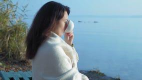 O close-up, mulher bonita em uma manta com um copo do chá senta-se no banco e nos olhares de rio no nascer do sol vídeos de arquivo