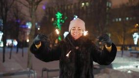 O close-up, mulher feliz balança luzes de Bengal no parque da noite para o Natal filme