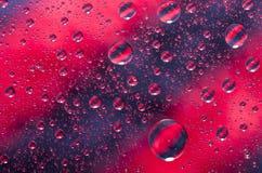 O close-up na água deixa cair o fundo na superfície do vermelho e do preto wat fotografia de stock