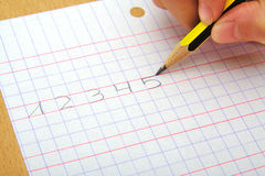 O close up na mão de uma escrita da criança numera Fotografia de Stock Royalty Free