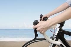 O close up na mulher entrega a montada de uma bicicleta Fotografia de Stock Royalty Free