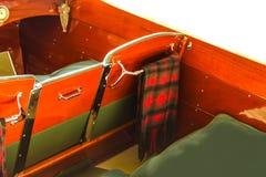O close-up no interior do barco a motor clássico do woodend com cobertura da manta drapejou no gancho do cromo sobre para trás do fotos de stock