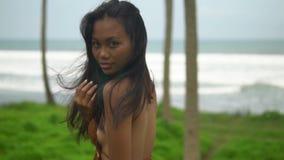 O close-up, poses da jovem mulher do lento-movimento na praia do oceano, menina olha na câmera filme