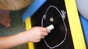 O close-up, posses da mão das crianças risca à disposição, tira um desenho do quadro, imagem no quadro-negro video estoque