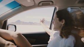 O close-up POV disparou da mulher feliz com cabelo do voo em um carro que move demasiado rápido ao longo do deserto do lago de sa vídeos de arquivo