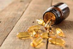 O close up suplementa a garrafa das vitaminas no fundo de madeira Imagem de Stock Royalty Free
