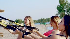 O close-up, três atléticos, jovens mulheres 'sexy' nos roupas de banho, instrutores, fazendo exercita com sistema do trx da aptid vídeos de arquivo