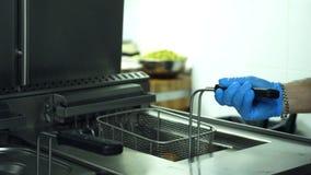 O close-up, um cozinheiro nas luvas guarda uma grade especial para batatas da repreensão o cozinheiro cozinha partes de batatas,  video estoque