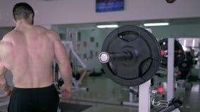 O clube de esporte, halterofilista muscular desencapado-chested põe o disco sobre o barbell à imprensa de banco durante o treinam video estoque