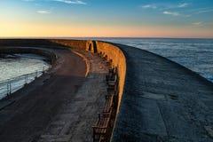 O Cobb em Lyme Regis varre para fora ao mar, com o sol que aumenta e que incandesce do céu fotografia de stock