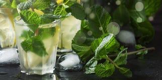 O cocktail alco?lico, ch? da hortel? com rum em vidros pequenos com gelo em um cora??o deu forma ao fundo de madeira do vintage,  foto de stock