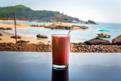 O cocktail da morango com uma palha em um vidro está na tabela no fundo do mar Imagens de Stock Royalty Free