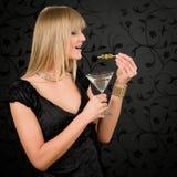 O cocktail da preensão do vestido de partido da mulher come azeitonas Imagem de Stock