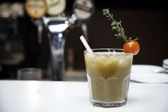 O cocktail vegetal em um vidro com um tubo decorou com um tomate com um ramo na perspectiva de uma barra obscura Fotos de Stock