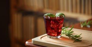 O cocktail vermelho com o gelo, decorado com a folha da hortelã na placa de corte de madeira com alecrins próximo, registra no fu Fotografia de Stock