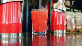 O cocktail vermelho derramou em um vidro video estoque